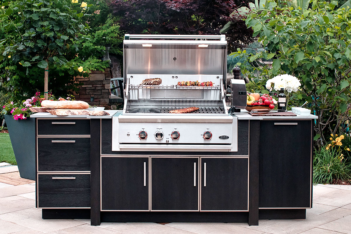 An outdoor kitchen set with the barbecue turned on, grilling ribs and skewers