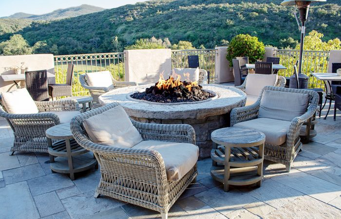 A beautiful stone fire pit on the patio with lounge chairs around it